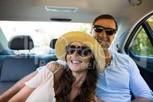 Cheerful couple wearing sunglasses in car