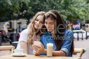 Friends using mobile phone while sitting on chairs