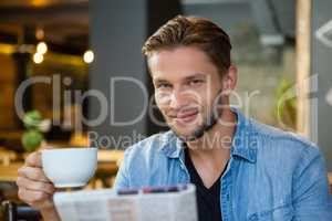 Portrait of handsome man holding coffee cup