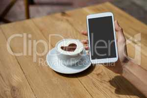 Close up of woman photographing coffee cup on table