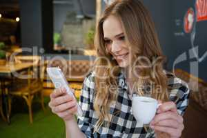 Smiling woman using mobile phone while holding coffee cup