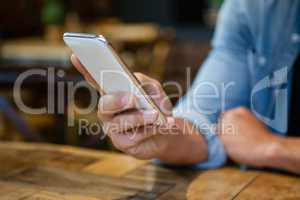 Cropped image of man using smart phone at table
