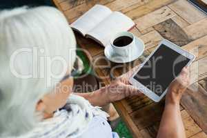 Close up of woman using tablet on table