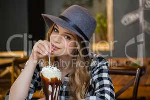Portrait of woman wearing hat drinking cold coffee