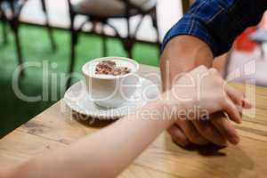Couple holding hands by coffee cup on table