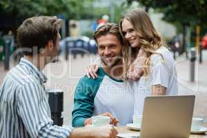 Couple looking at friend while sitting at sidewalk cafe