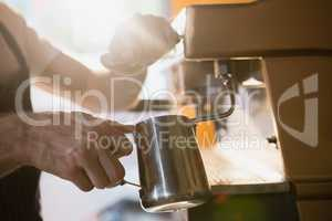 Mid section of waiter pouring milk in jug from coffee machine