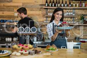 Portrait of smiling waitress holding a chocolate cake at counter
