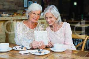 Two senior women using digital tablet