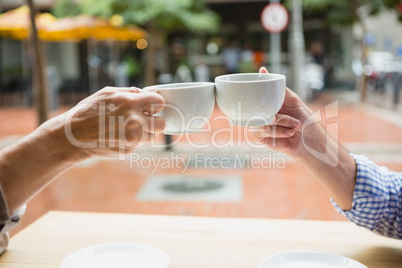 Hands of senior couple toasting coffee cups