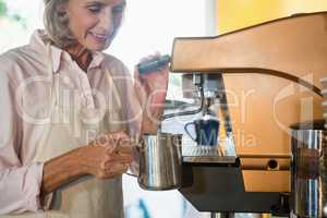 Senior waitress using coffeemaker