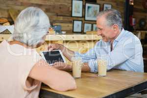Senior couple using digital tablet while having coffee