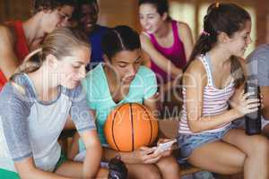 High school kids using mobile phone while relaxing in basketball court