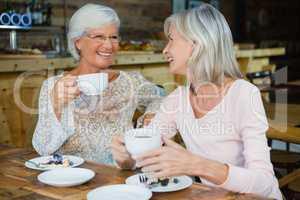 Happy senior friends having coffee and breakfast