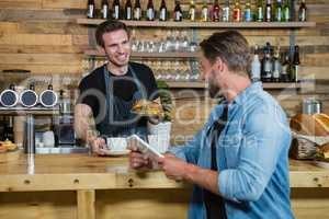 Waiter serving coffee to male customer at counter