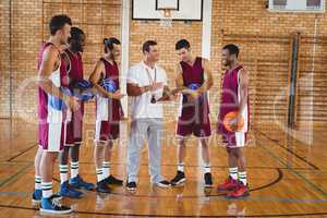 Coach interacting with basketball players