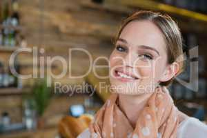 Portrait of woman standing near counter in cafe