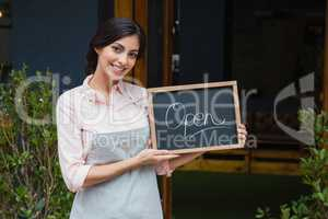 Portrait of waitress holding open signboard at the entrance
