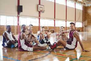 Smiling basketball player relaxing in the court