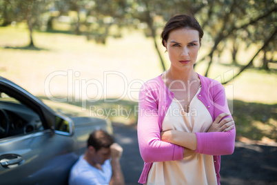 Angry woman standing with man sitting by breakdown car