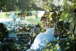 Senior man driving car seen through rear windshield