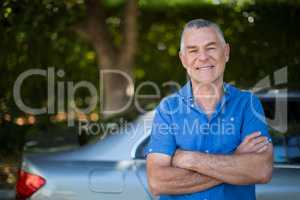 Senior man with arms crossed standing by car