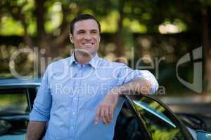 Smiling man leaning on car door