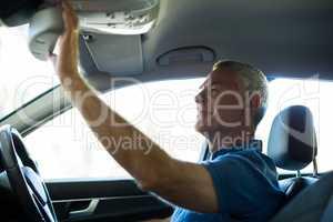 Senior man adjusting rear view mirror in car