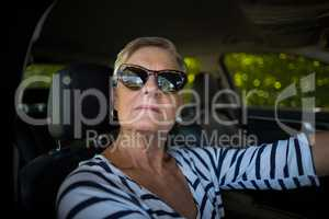 Serious senior woman driving car