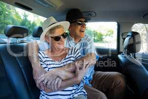 Senior couple enjoying on car back seat