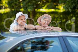 Senior couple leaning on car roof