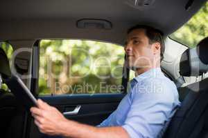 Man holding digital tablet in car