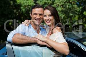 Happy couple leaning on car door