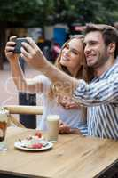 Cheerful couple holding smart phone while sitting at sidewalk cafe