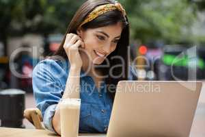 Smiling woman using laptop while sitting at sidewalk cafe