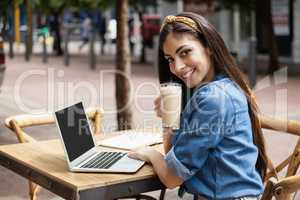 Portrait of woman using laptop while sitting at cafe