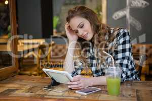 Woman using table computer while sitting at table