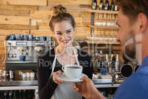 Smiling owner giving coffee to customer