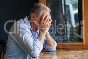 Senior man covering face while sitting at table
