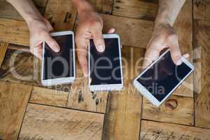 Close up of friends holding mobile phone on table