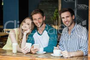 Portrait of smiling friend holding smart phone while sitting by table