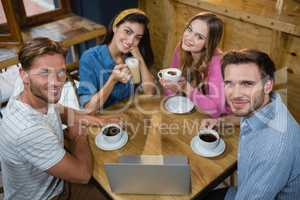 Portrait of happy friends having coffee at table