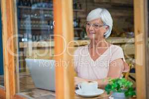 Senior woman talking on mobile phone while having coffee
