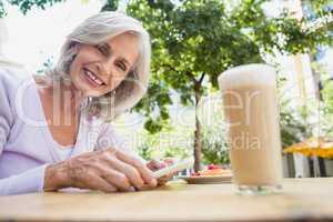 Portrait of senior woman holding mobile phone