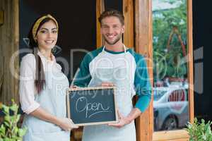 Portrait of smiling waiter and waitress standing with chalkboard