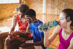 High school girl drinking water while boys using mobile phone