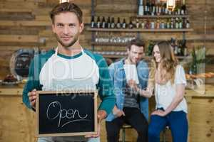Waiter holding chalkboard with open sign and customer in background