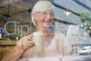 Happy senior woman using mobile phone while having cold coffee