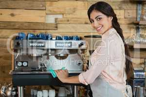 Portrait of waitress cleaning coffeemaker machine