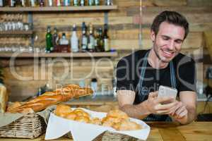 Waiter using mobile phone at counter